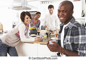 Eine Gruppe junger Freunde bereitet Frühstück in der modernen Küche vor