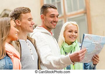 Eine Gruppe von Freunden mit Landkarten, die die Stadt erkunden.