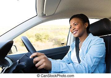 Eine junge Afrikanerin, die ein Auto fährt.