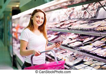 Eine junge Frau kauft im Supermarkt ein