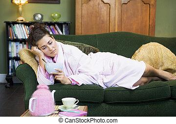 Eine junge Frau liegt auf ihrer Couch und isst Müsli