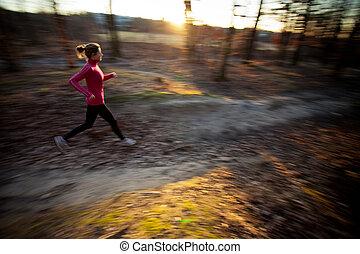Eine junge Frau rennt draußen in einem Stadtpark herum