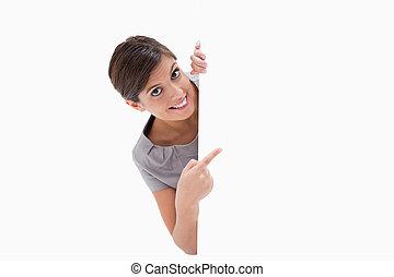 Eine lächelnde Frau, die um die Ecke zeigt.