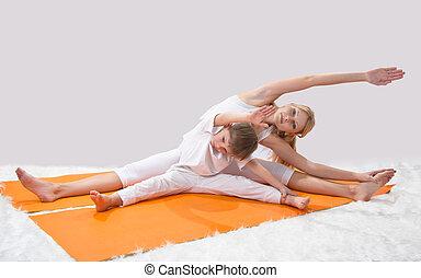 Eine schöne junge Mutter übt Yoga mit ihrem Sohn