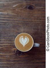 Eine Tasse Cappuccino-Kaffee mit Latte-Kunst auf dem Tisch.