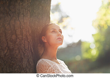 Einfühlsame junge Frau lehnt sich an den Baum.