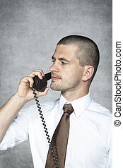 Ernster Geschäftsmann, der am Telefon redet.