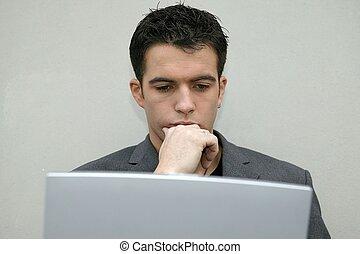 Ernsthafter Mann, der auf seinen Laptop schaut.