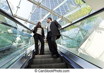 Führungskräfte auf einem Escalator.