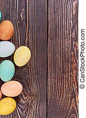 Farbige Eier auf braunem Holz.