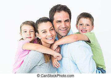 Fröhliche junge Familie, die zusammen Kamera sieht.