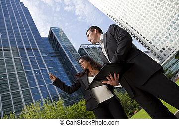Fröhliches gemischtes Geschäftsmann- und Geschäftsfrau-Team in der Stadt.