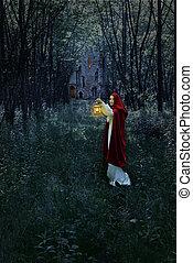 Frau mit Laterne im Wald.