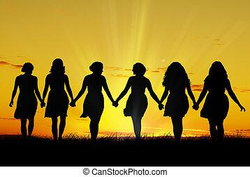 Frauen gehen Hand in Hand.