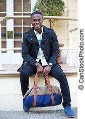 Freundlicher junger Mann, der vor dem Hotel mit Tasche sitzt.
