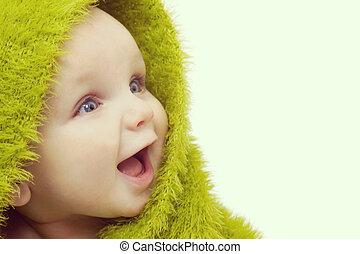 Frohes Baby in grüner Decke.