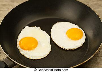 Gebratenes Ei in einer Pfanne aus Holz.