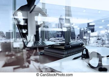 Geschäftsdokumente auf Bürotisch mit Smartphone und digitaler Tafel und London Stadt verschwommene Sicht und Menschen denken im Hintergrund.
