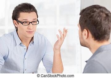 Geschäftskommunikation. Zwei vertrauensvolle Geschäftsleute in zwangloser Kleidung, die über etwas und Gestümmel reden