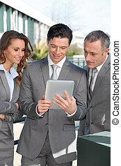 Geschäftsleute treffen sich draußen mit elektronischer Tafel