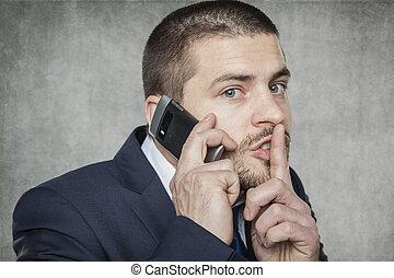 Geschäftsmann am Telefon und bittet um Ruhe.