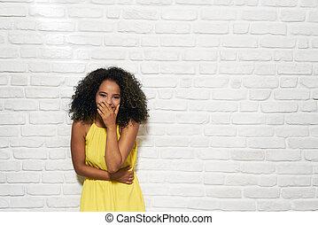 Gesichtsausdrücke der jungen schwarzen Frau an der Mauer