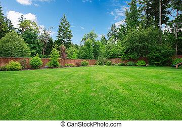 Grüner großer Garten mit Bäumen.