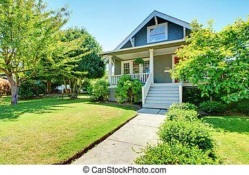 Graue kleine amerikanische Hausfront mit weißer Treppe.