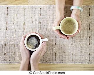 Hände mit Kaffee.