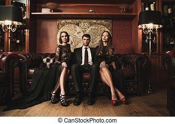 Hübsche Brünette mit Anzug auf dem Sofa mit zwei schönen Frauen.