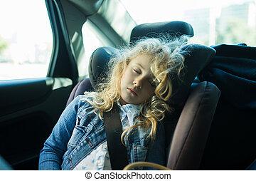 Hübsches blondes Mädchen, das auf einem Autositz schläft.