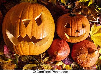 Halloween-Kürbisse, geschnitzte Jack-O-Lantern in Herbstblättern