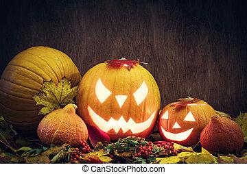 Halloween Kürbisse glühen, geschnitzte Jack-O-Lantern in Herbstblättern