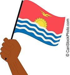 Hand hält und hebt die nationale Flagge von Kiribati.