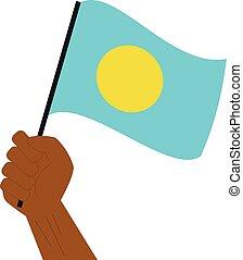 Hand hält und hebt die nationale Flagge von Palau.