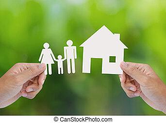 Hand halten Haus und Familie auf Grün.