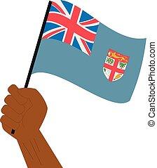 Hand halten und die nationale Flagge von Fidschi erheben.