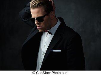 Harter, scharf gekleideter Mann in schwarzem Anzug.