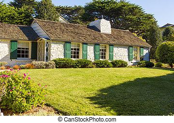 Haus mit großem Rasen und Bäumen.
