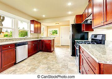 Heller Küchenraum mit schwarzen und Stahlgeräten.