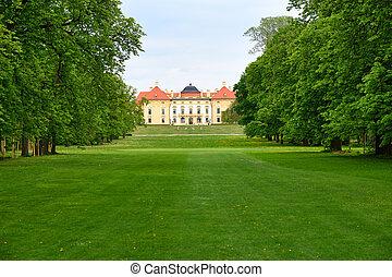 Historisches Schloss mit grünen Bäumen und Rasen im Frühling.