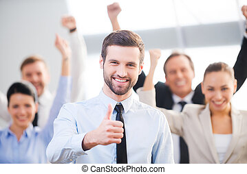 Ich bin zuversichtlich in seinem Team. Glücklicher Geschäftsmann, der seinen Daumen zeigt und lächelt, während seine Kollegen im Hintergrund stehen