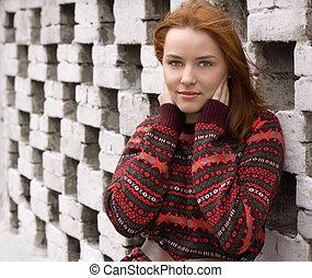 Im Freien Porträt einer schönen rothaarigen Frau in roter Jacke