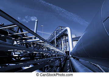 Industrieleitungen auf Rohrbrücke gegen Himmel in blauem Ton