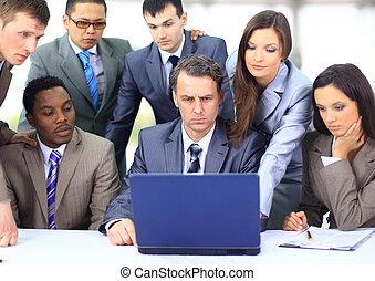Interracial Business Team arbeitet an einem Laptop in einem modernen Büro
