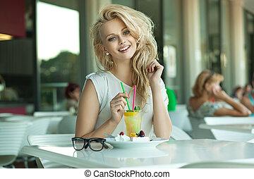 Junge, fröhliche Blondine in einer Trinkbar
