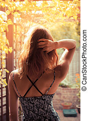Junge Frau im Garten bei Sonnenaufgang.