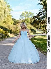 Junge Frau in blauem Ballkleid im Garten.
