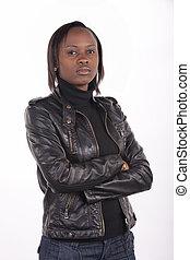 Junge südafrikanische Frau mit schwarzem Leder und ein ernster Ausdruck auf weißem Hintergrund.