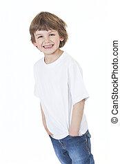 Junger, glücklicher Junge, lächelnde Hände in den Taschen